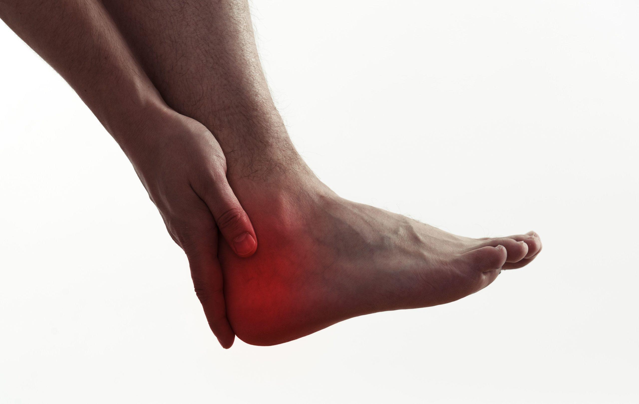 Imagem de uma pessoa sentindo dores no tendão na região do pé.