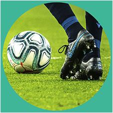 Imagem ilustrativa de uma pessoa no campo de futebol com chuteira e uma bola